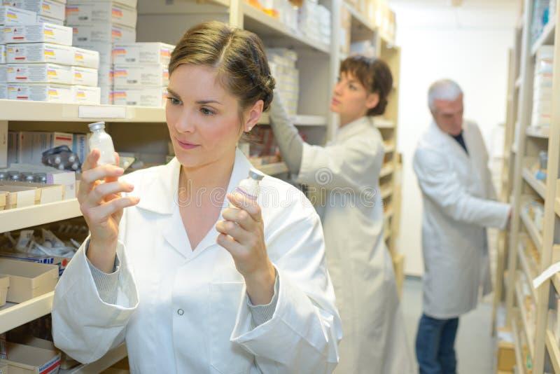Farmacêutico que olha a medicamentação para a prescrição na farmácia imagens de stock royalty free