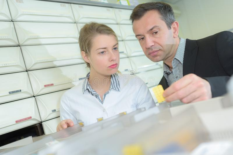 Farmacêutico que olha o recipiente da prescrição e da medicina na farmácia foto de stock royalty free