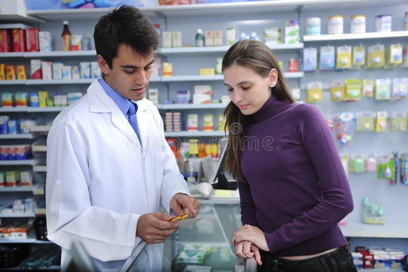 Farmacêutico que recomenda o cliente na farmácia imagem de stock royalty free