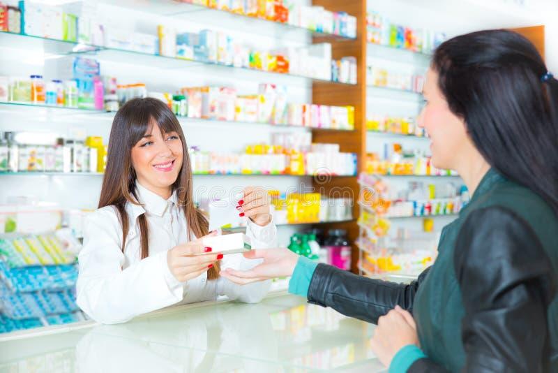 Farmacêutico que sugere a droga médica ao comprador na farmácia fotografia de stock