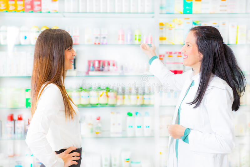 Farmacêutico que sugere a droga médica ao comprador na farmácia fotos de stock