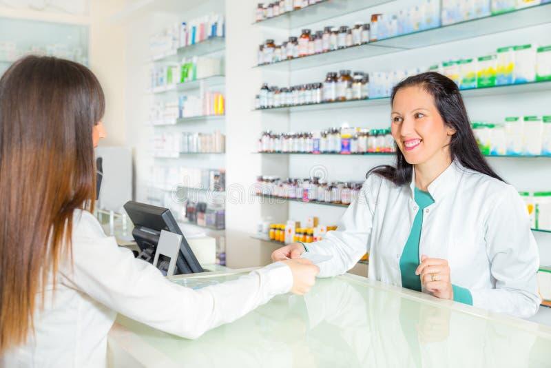 Farmacêutico que sugere a droga médica ao comprador na farmácia foto de stock royalty free