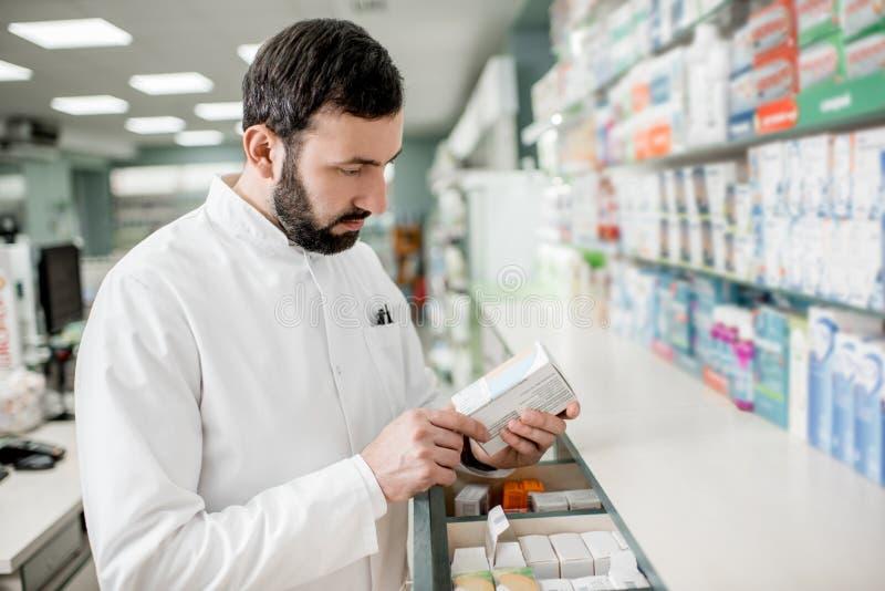 Farmacêutico que trabalha na loja da farmácia foto de stock