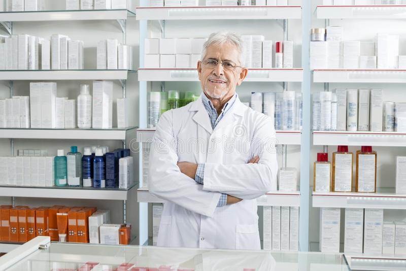 Farmacêutico seguro Standing Arms Crossed na farmácia imagens de stock royalty free