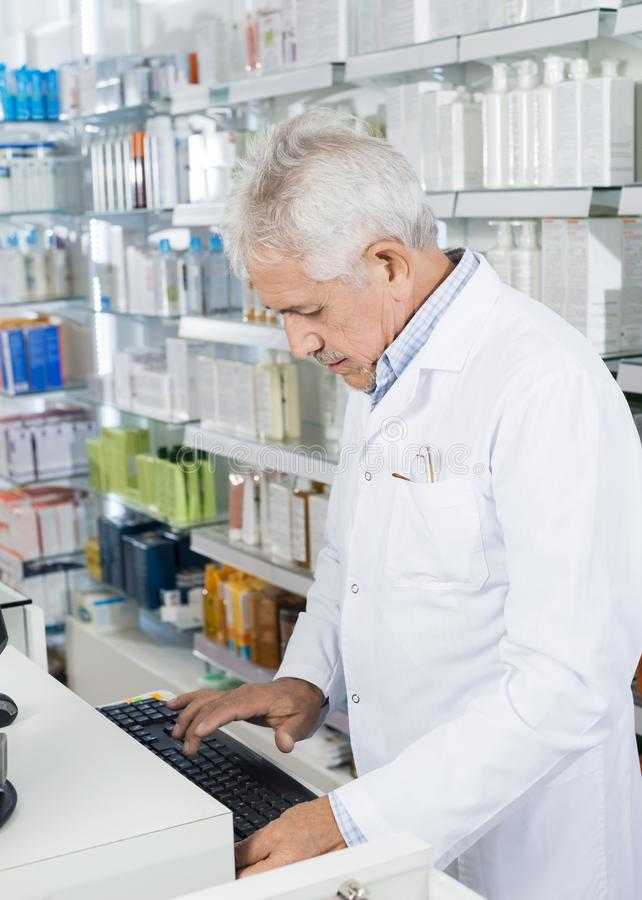 Farmacêutico Using Computer Keyboard no contador foto de stock