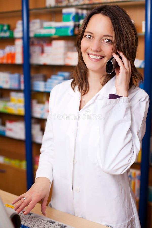 Farmacêutico Using Cordless Phone na mesa fotografia de stock royalty free