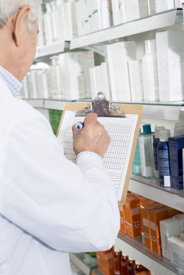 Farmacêutico Writing On Clipboard ao contar o estoque na farmácia imagens de stock