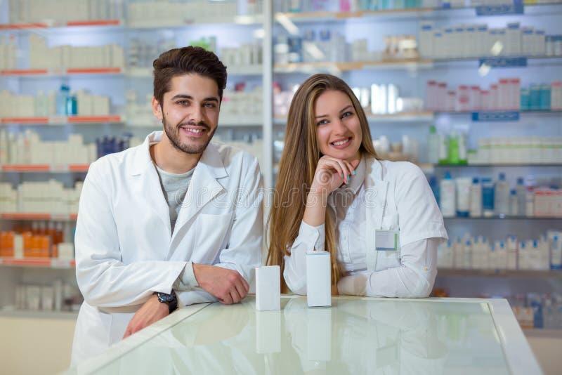 Farmacêuticos fêmeas e masculinos na farmácia imagens de stock