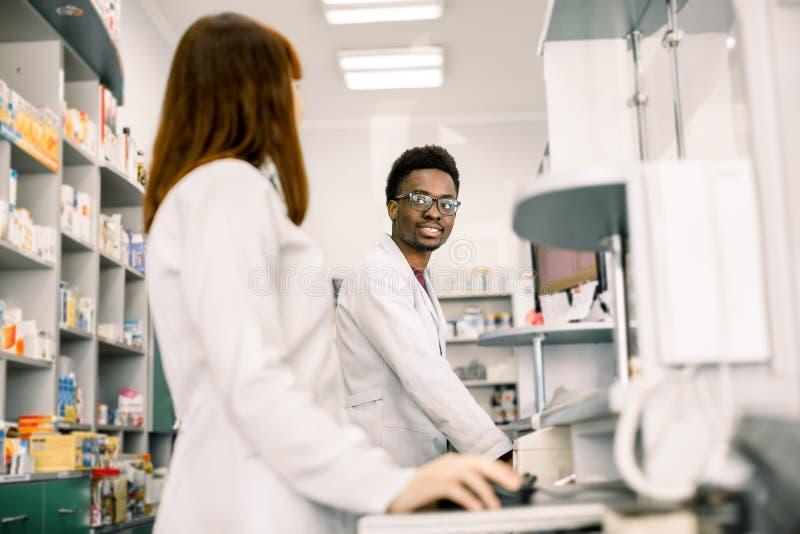 Farmacêuticos fêmeas e masculinos na farmácia moderna, olhando se, ao trabalhar em computadores foto de stock