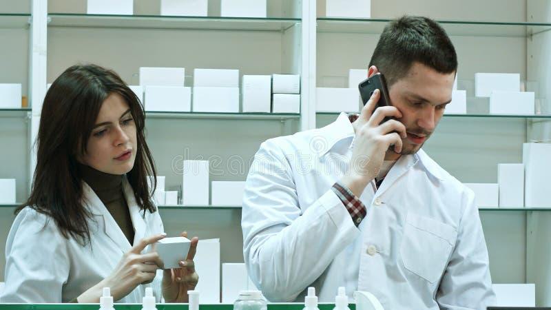 Farmacêuticos fêmeas e masculinos que trabalham na farmácia, falando através do telefone esperto e verificando comprimidos foto de stock royalty free