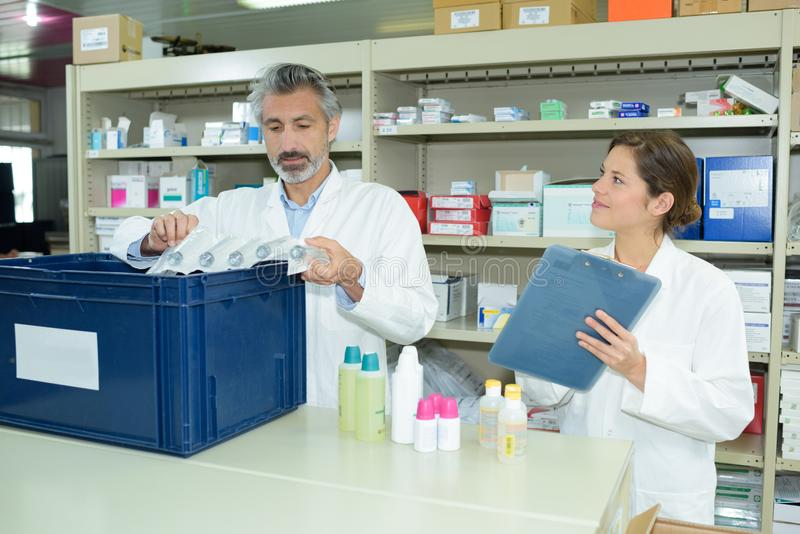 Farmacêuticos masculinos e fêmeas que mantêm a lista de verificação no contador na farmácia fotografia de stock
