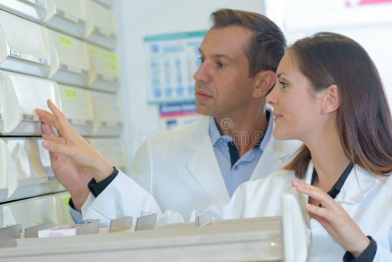 Farmacêuticos que olham a medicamentação na gaveta imagens de stock