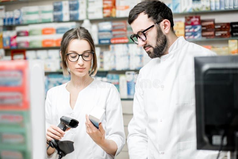 Farmacêuticos que trabalham na loja da farmácia imagens de stock royalty free
