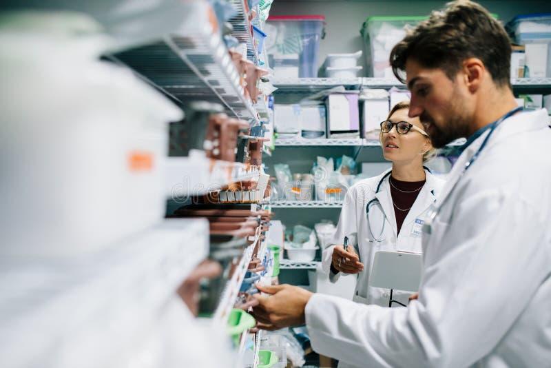 Farmacêuticos que verificam o inventário na farmácia do hospital fotos de stock