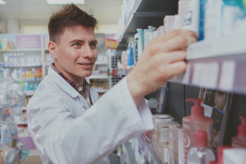 Farmac?utico de sexo masculino hermoso que trabaja en su droguer?a imagen de archivo libre de regalías
