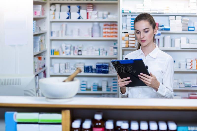 Farmaceuta patrzeje w schowku przy kontuarem obrazy stock