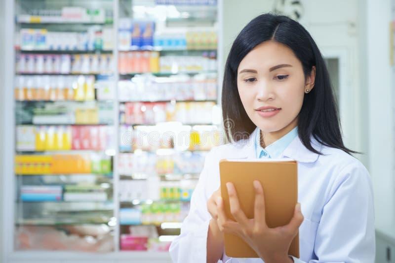 Farmaceuta pracuje z pastylka komputerem w aptece trzyma je w jej r?ce podczas gdy czytaj?cy informacj? zdjęcia stock