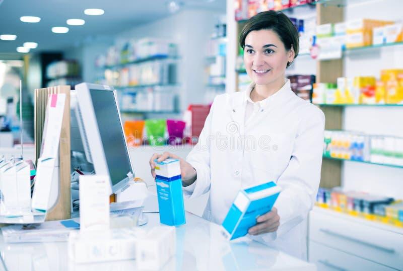 Farmaceuta przygotowywająca pomagać w wybierać przy kontuarem obrazy stock