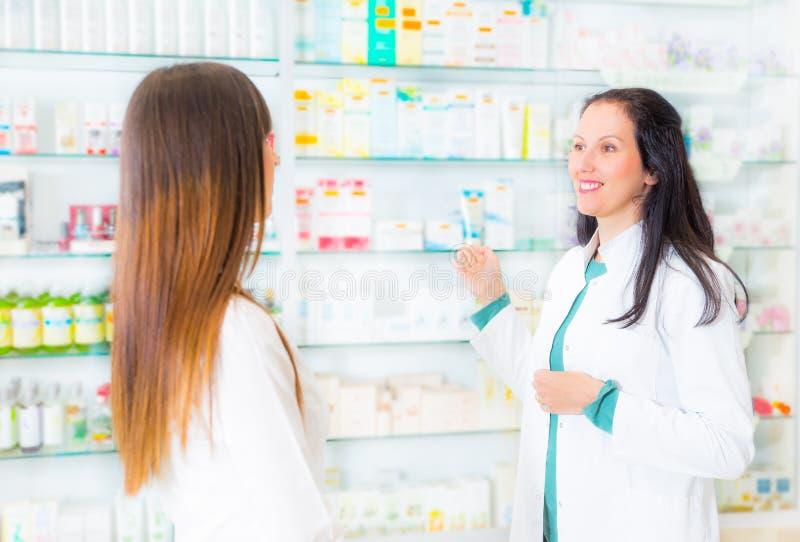 Farmaceuta sugeruje medycznego leka nabywca w aptece zdjęcia royalty free