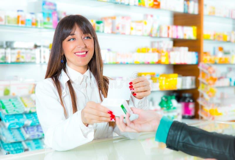 Farmaceuta sugeruje medycznego leka nabywca w apteki aptece zdjęcie royalty free