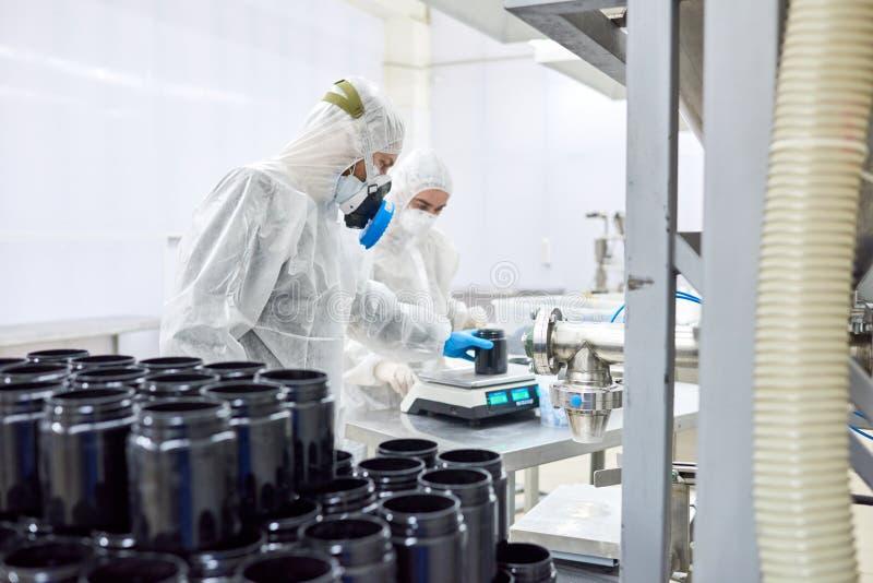Farmaceutische Installatiearbeiders die Schaal gebruiken stock foto