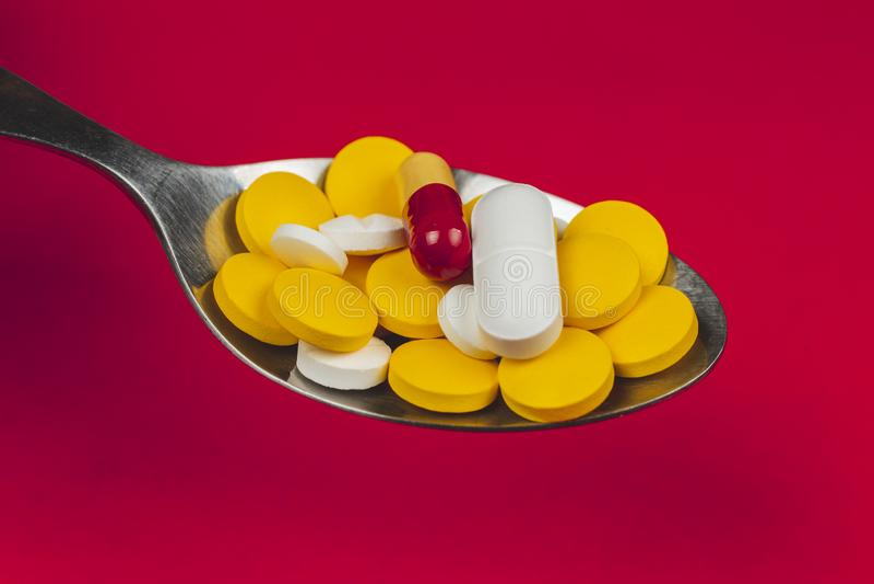 Farmaceutiska medicinpiller, på skeden mot röd bakgrund arkivbild