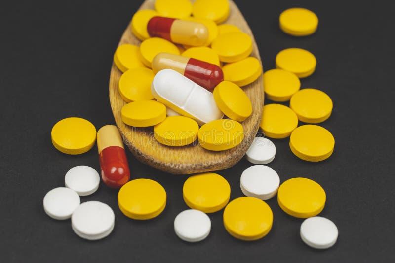 Farmaceutiska medicinpiller, på träskeden på svart bakgrund fotografering för bildbyråer