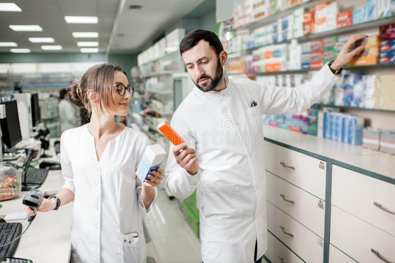 Farmaceuty pracuje w apteka sklepie obrazy royalty free