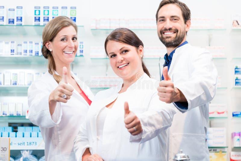 Farmaceuty w aptece pokazuje aprobaty obraz royalty free