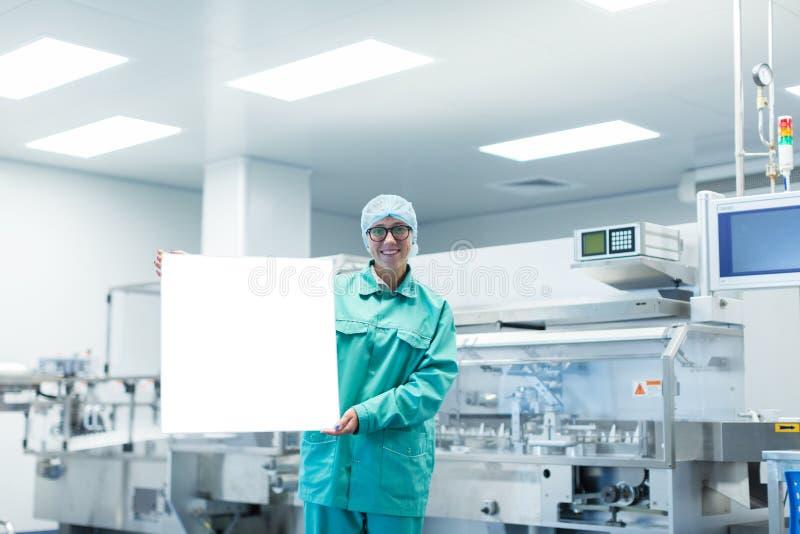 Farmaceutyczny pracownik fabryczny pokazuje wyposażenie obraz royalty free