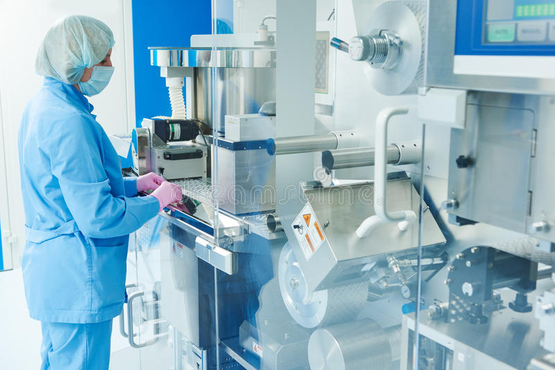 farmacie De farmaceutische arbeider stelt blaar verpakkende machine in werking stock foto