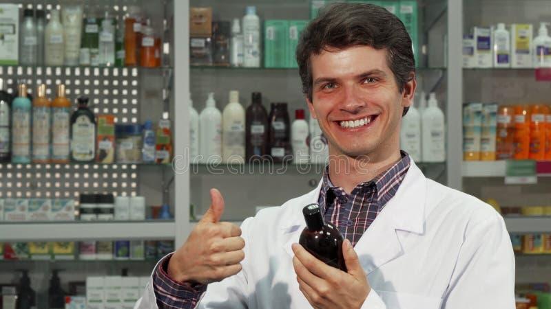 Farmacista allegro che mostra i pollici su mentre lavorando alla farmacia fotografia stock libera da diritti