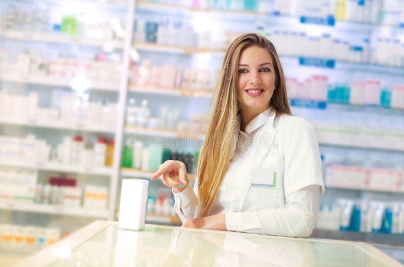 Farmacista attraente sorridente della donna che visualizza una scatola di compresse o un prodotto in sue mani fotografie stock