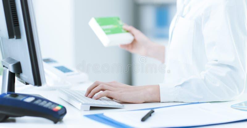 Farmacista che cerca i prodotti nella base di dati immagini stock