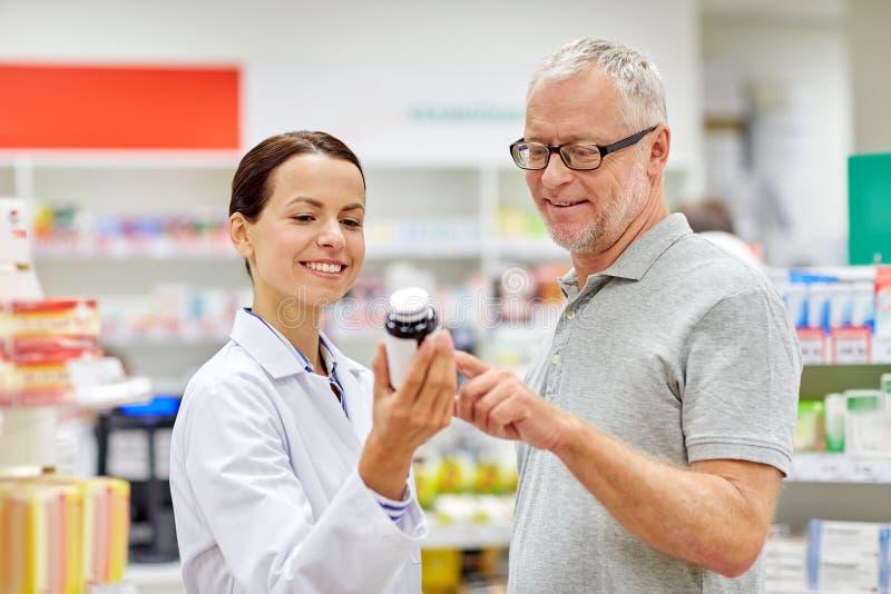 Farmacista che mostra droga all'uomo senior alla farmacia fotografie stock