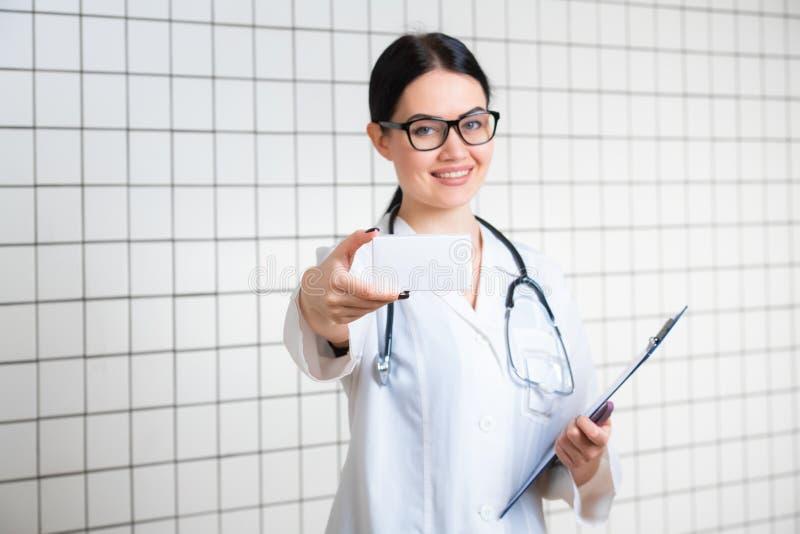 Farmacista che mostra la scatola in bianco bianca della medicina con il fondo dell'ufficio della farmacia fotografia stock