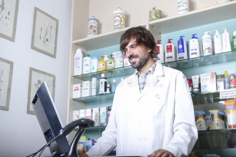 Farmacista che per mezzo di un computer fotografia stock libera da diritti