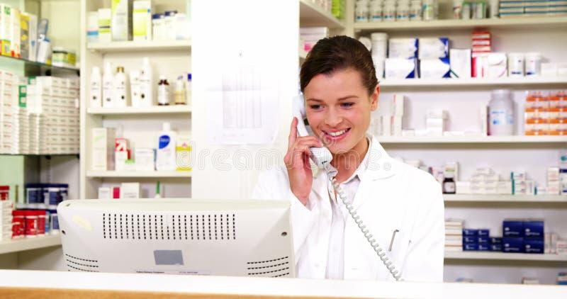 Farmacista che sta al contatore e che parla sul telefono video d archivio