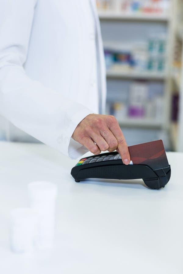 Farmacista che swiping carta tramite il terminale di pagamento fotografia stock