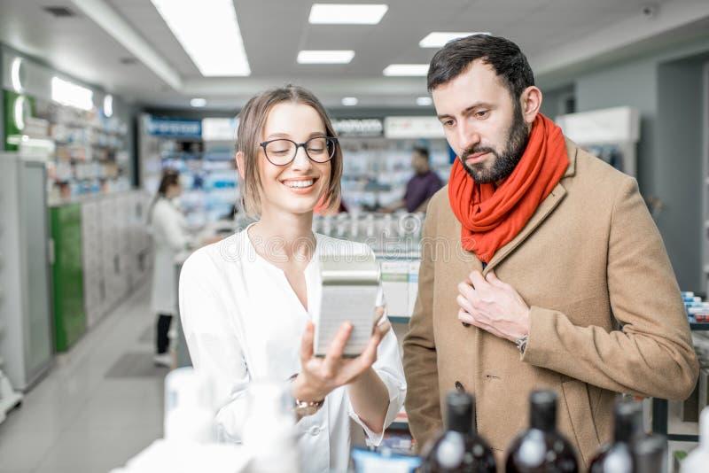 Farmacista con il cliente nel deposito della farmacia fotografie stock