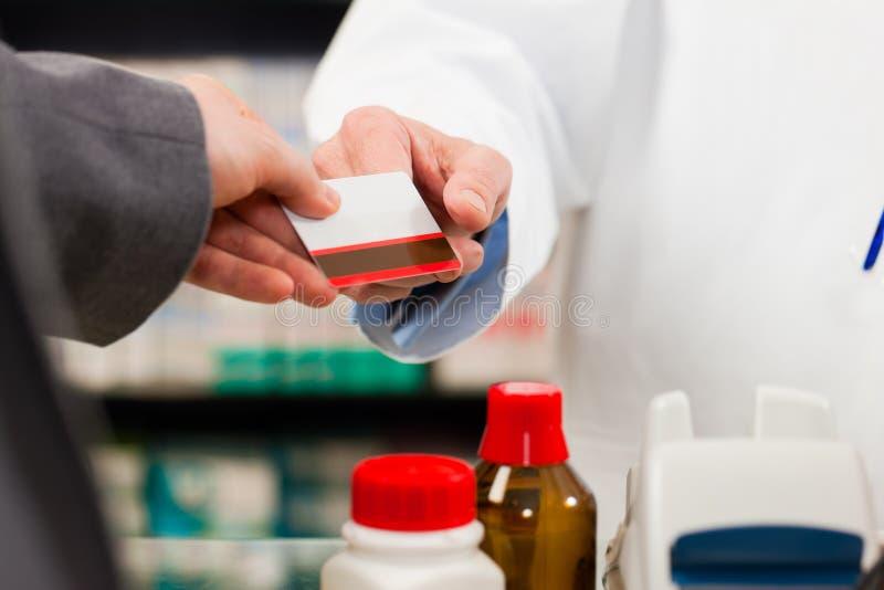 Farmacista con il pagamento del cliente in farmacia fotografia stock libera da diritti
