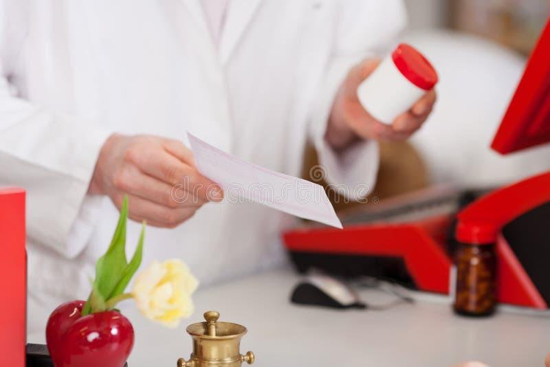 Farmacista con la bottiglia e la prescrizione della medicina fotografia stock