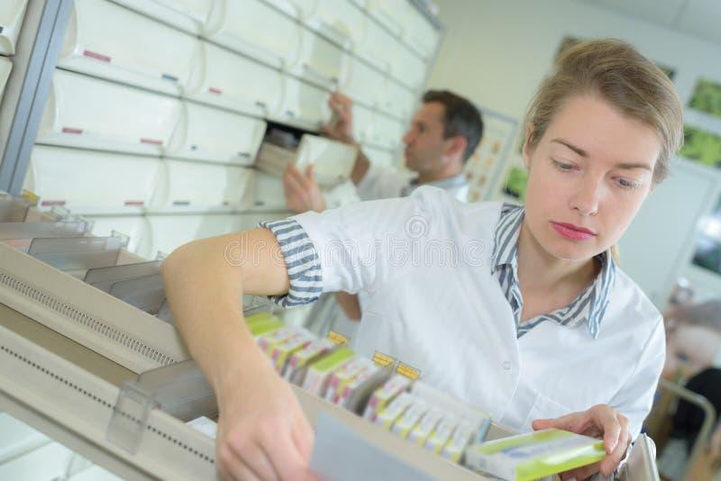 Farmacista d'erogazione che prende le compresse dal cassetto fotografie stock