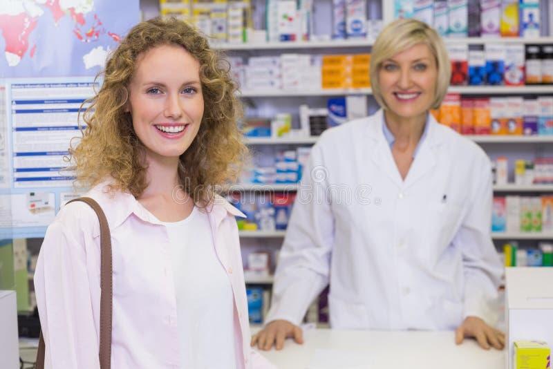 Farmacista e cliente sorridenti che discutono un prodotto fotografie stock