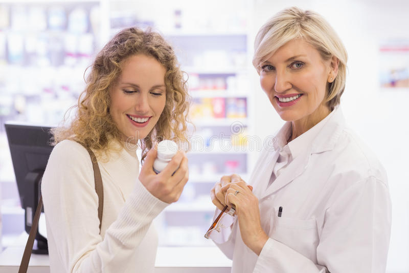 Farmacista e cliente sorridenti che discutono un prodotto fotografie stock libere da diritti