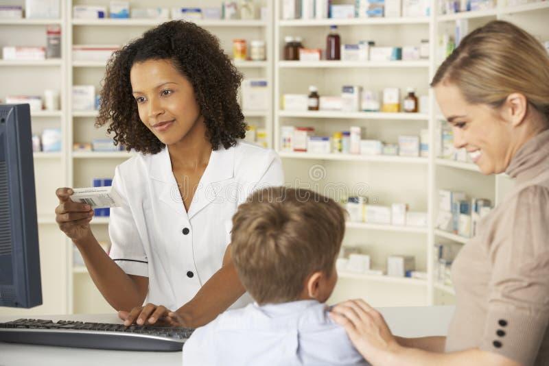 Farmacista in farmacia con la madre ed il bambino immagine stock libera da diritti