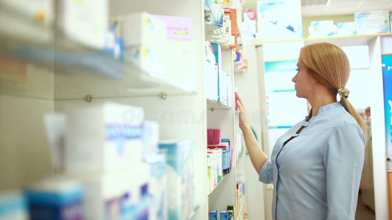 Farmacista femminile che sta al contatore in farmacia archivi video