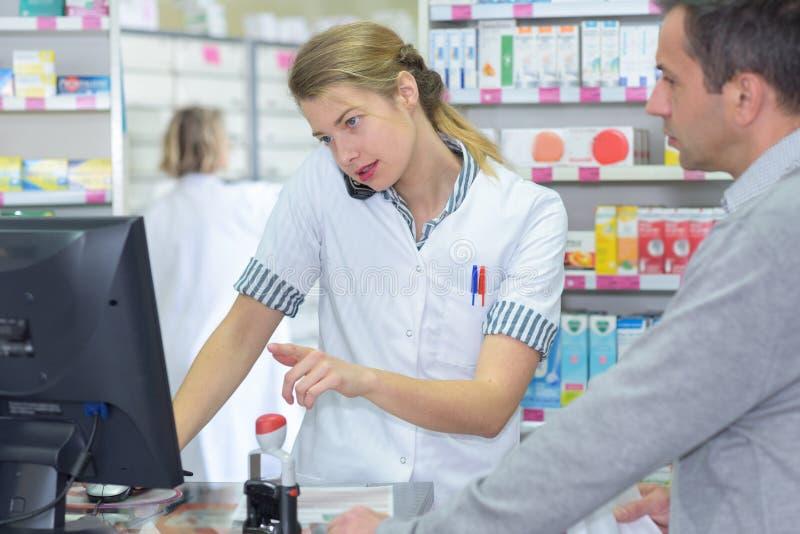 Farmacista femminile che verifica qualcosa in cliente anteriore immagini stock libere da diritti