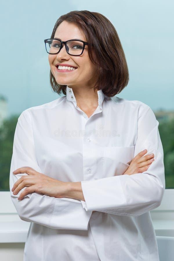 Farmacista femminile maturo Smiling, armi attraversate, finestra panoramica del fondo fotografie stock