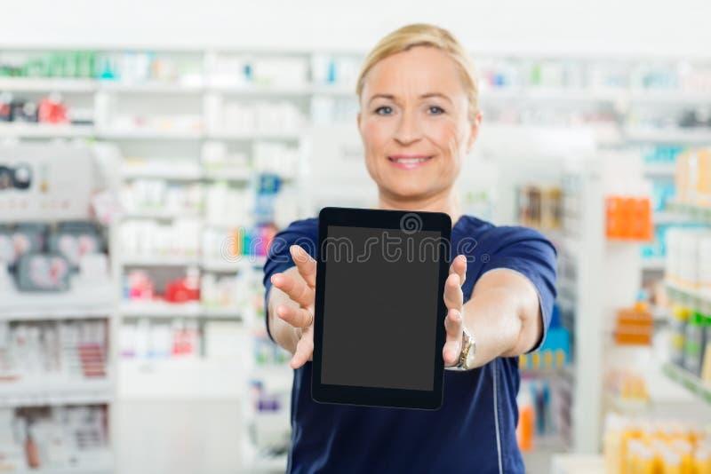 Farmacista femminile Showing Digital Tablet con fotografia stock libera da diritti